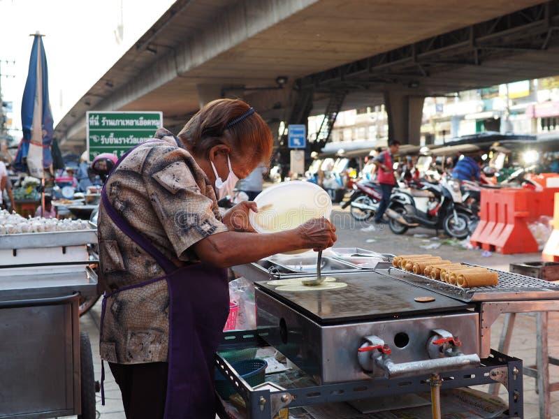 泰国妇女做香肠绉纱在一个地方市场上 免版税库存照片