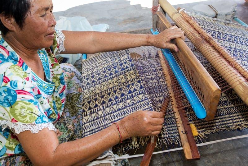 泰国妇女编织的秸杆席子 免版税库存图片