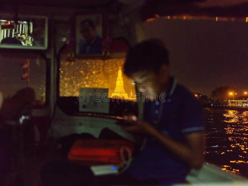 泰国少年乘沿Chaopraya河的小船航行在黎明寺附近 库存照片