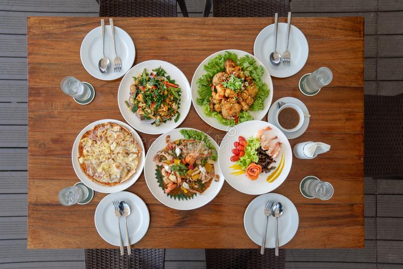 泰国应用的午餐集合例如海鲜油煎用调味汁、比萨、三文鱼沙拉和炸虾在木桌上从顶视图 免版税库存图片