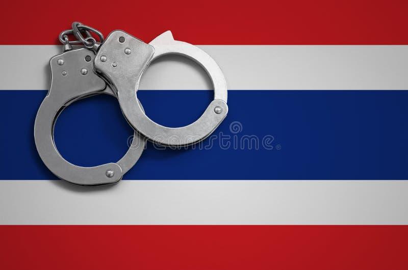 泰国旗子和警察手铐 罪行和进攻的概念在国家 免版税库存照片