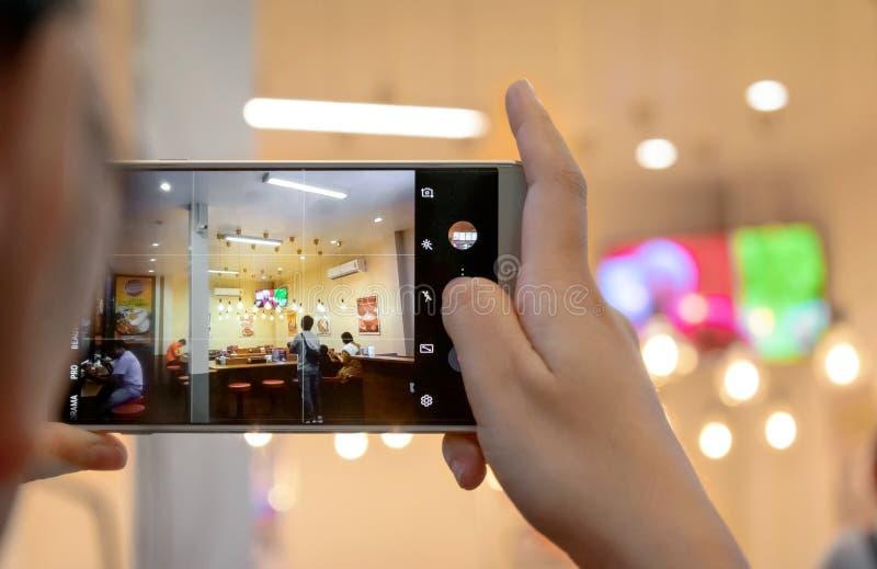 泰国曼谷- 6月15日:未命名的晚餐用手机拍照 免版税库存照片