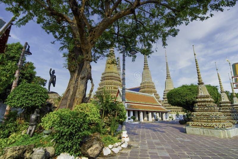 泰国曼谷Wat Poh的泰国古代艺术建筑,有塔楼和雕像,阳光明媚,天空美丽 免版税库存图片
