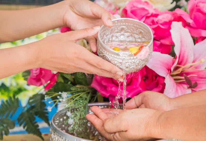 泰国松克兰节的标志:年轻人的手,浇水,浇花 泰国人在新年水中庆祝松克兰 库存图片