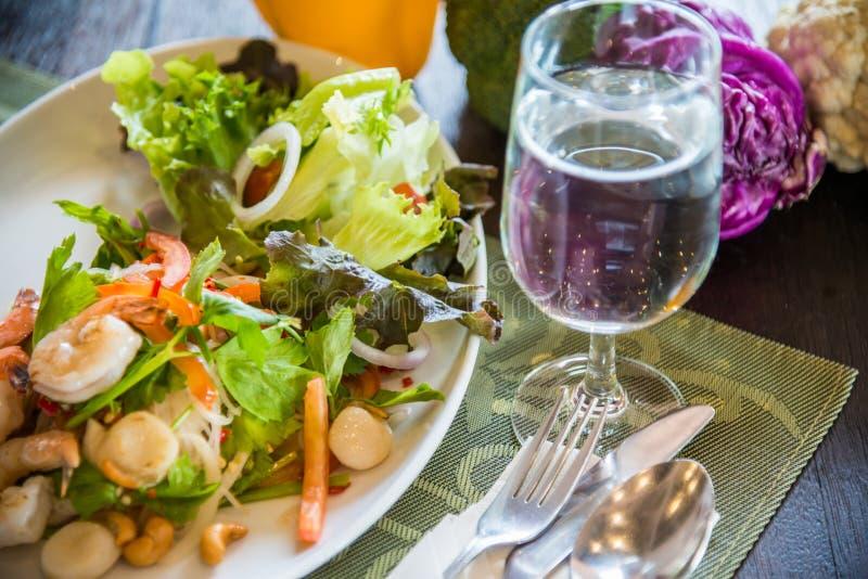 泰国样式沙拉盘与利器,杯的水 免版税库存照片