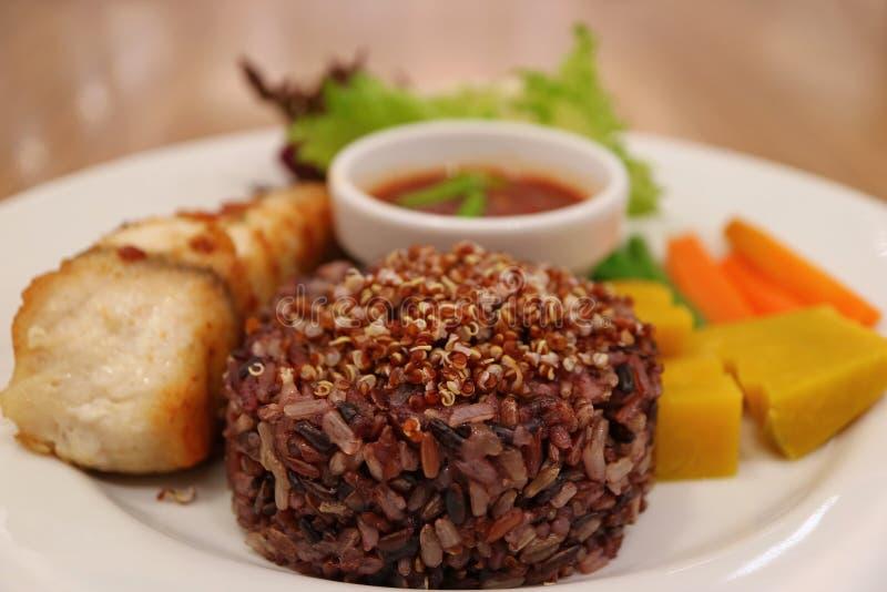 泰国样式蒸米莓果米用奎奴亚藜、被弄脏的烤白色雪鱼和煮沸的菜在背景中 免版税库存图片