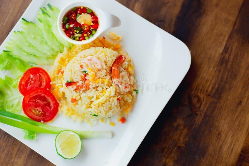 泰国样式虾炒米食谱顶视图在与菜装饰的木桌上服务在白色盘 图库摄影