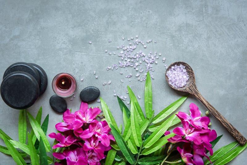 泰国温泉 设置为按摩治疗的热的石头顶视图和放松与在黑板的紫色兰花有拷贝空间的 ?? 库存照片