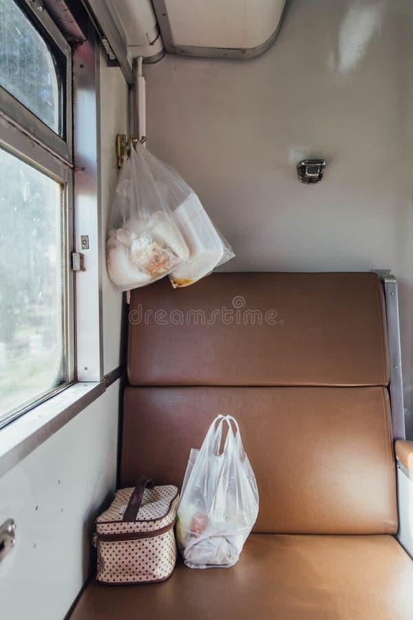泰国火车位子在窗口附近用在塑料袋和织品袋子的食物 免版税库存图片