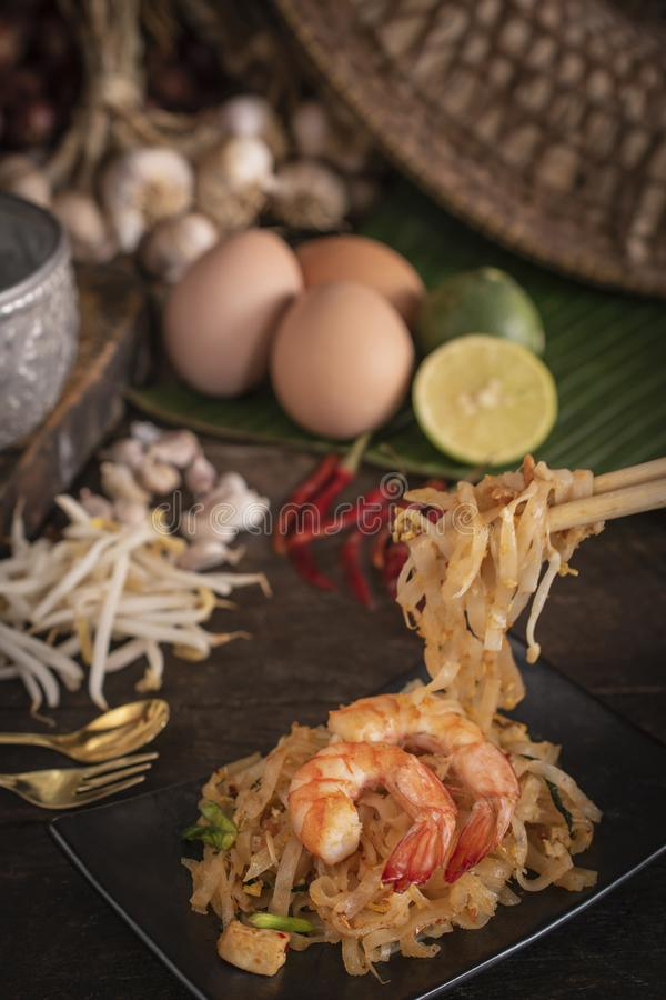 泰国炒面或垫泰语用虾在那里木桌安置的黑色的盘子是鸡蛋,大蒜,绿豆芽,青葱 免版税库存图片