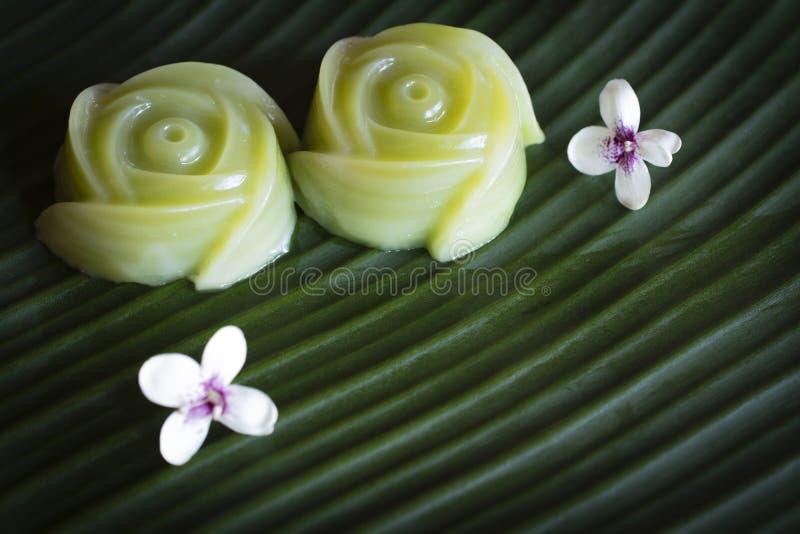 泰国点心分层堆积甜点结块有在香蕉叶子背景安置的白花 库存照片