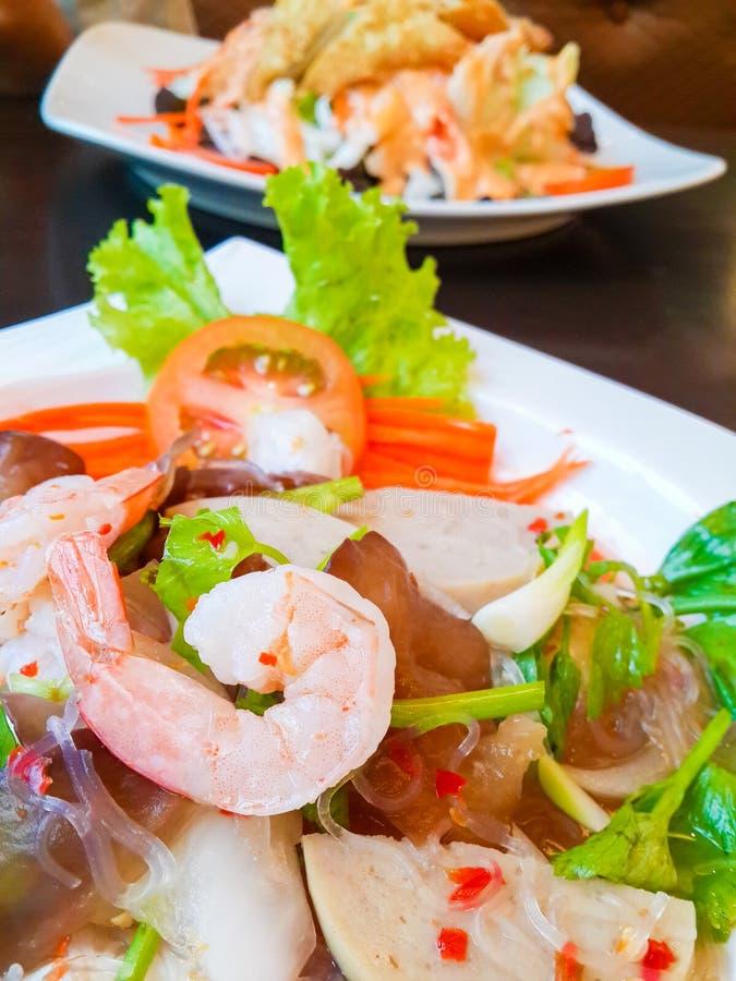 泰国烹调辣猪肉沙拉或辣猪肉的沙拉,虾,莴苣,鲜美的辣椒,在木桌上的泰国食物 免版税库存照片