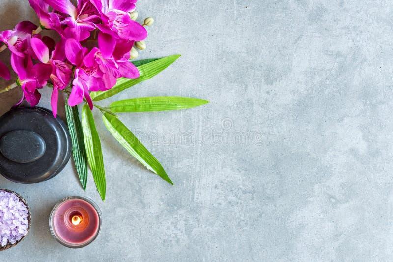 泰国的温泉 设置为按摩治疗的热的石头顶视图和放松与在黑板的紫色兰花有拷贝空间的 绿色 免版税库存照片