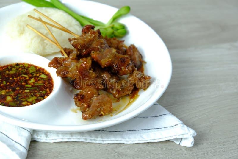 泰国的食物 与糯米和辣辣椒酱油食谱和绿色菜的烤猪肉格栅菜单在白色 免版税库存图片