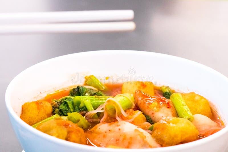泰国的食物 拿着筷子对肉丸 桃红色海鲜平的面条 辣柠檬香茅调味了汤用猪肉,鸡 库存照片