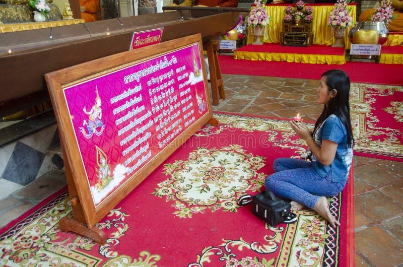 泰国祈祷在ubosot的妇女坐的尊敬大斜倚的菩萨雕象在Wat Phra非Chakkrasi Worawihan在信武里,Thaila 免版税库存照片