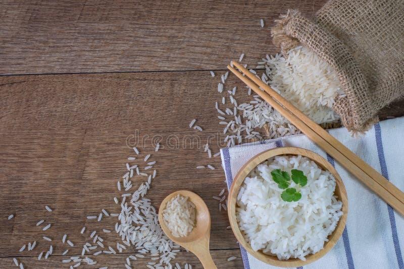 泰国米、煮熟的白米、煮熟的简单的米在木碗有匙子的和筷子,有机米在土气木, 库存照片