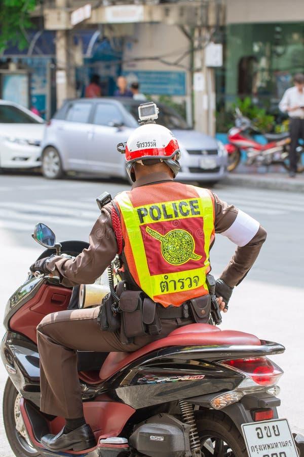 泰国警察当班与在头的motocycle和行动照相机 库存照片