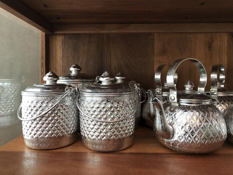 泰国银色葡萄酒罐和水壶,在木小猫存贮 库存图片
