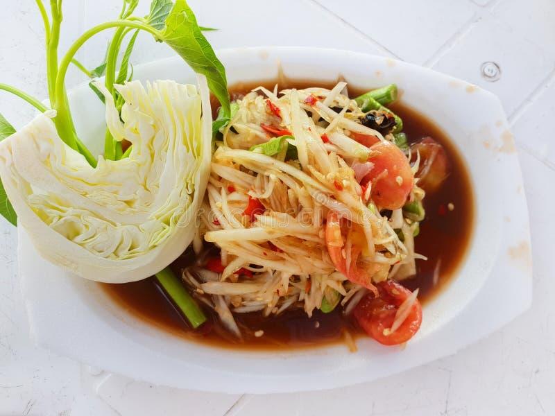 泰国食物样式、番木瓜沙拉用蕃茄,虾、辣椒、豆、牵牛花和圆白菜在白色板材 免版税库存照片