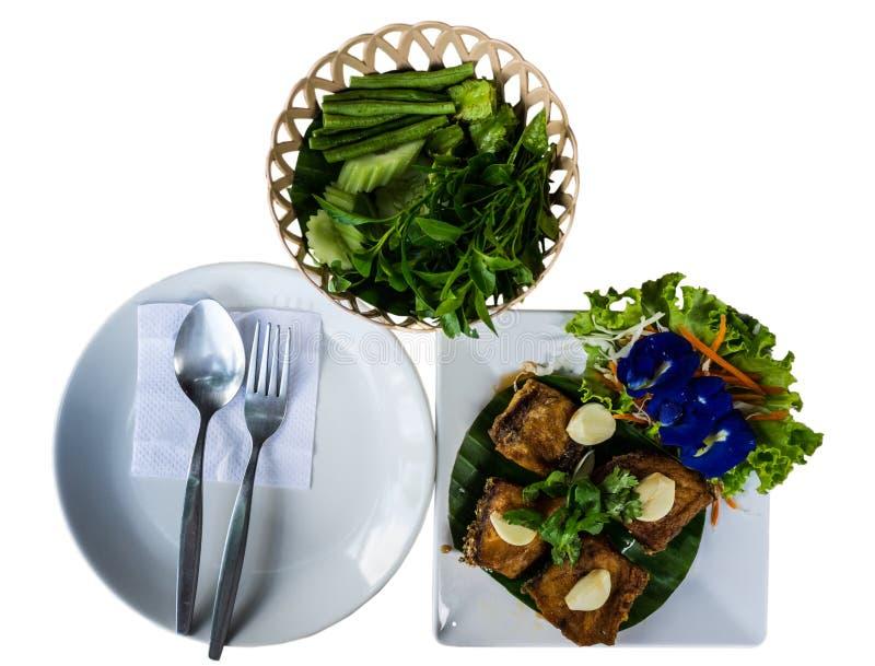 泰国食物,为做准备吃匙子叉子和盘与油煎的鱼和菜 库存照片