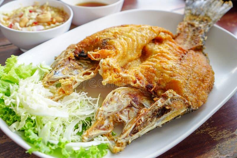 泰国食物,在白色板材的被油炸的Snappe在木表上 库存图片