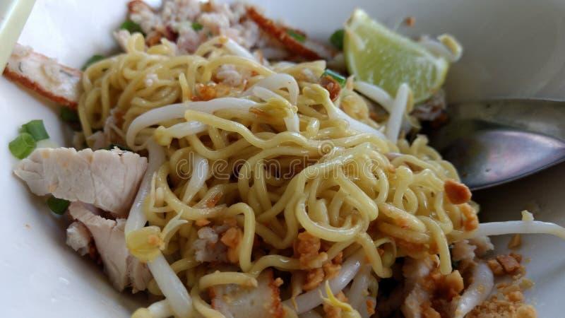 泰国黄色面条用猪肉切好的和鱼丸菜单 免版税库存照片