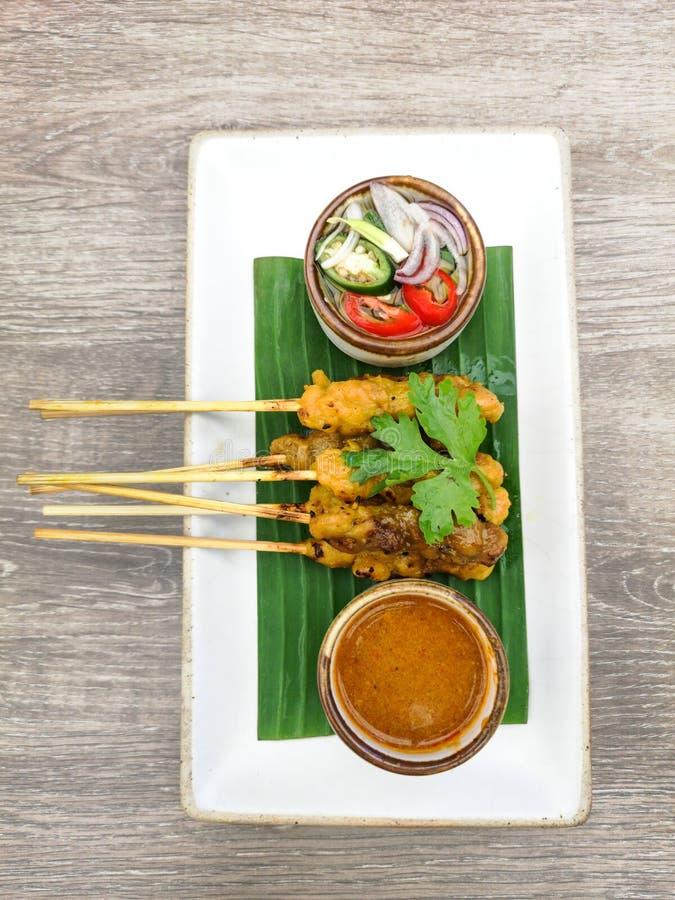 泰国satay鸡串用在香蕉叶子盖的板材的花生调味汁 免版税库存图片