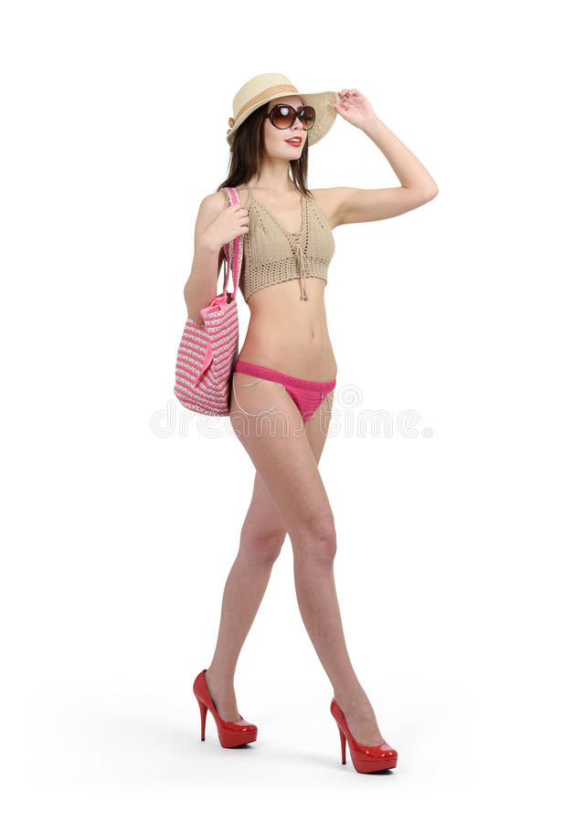 泳装、太阳镜和帽子的女孩在他的脚跟走 在空白背景 免版税库存照片