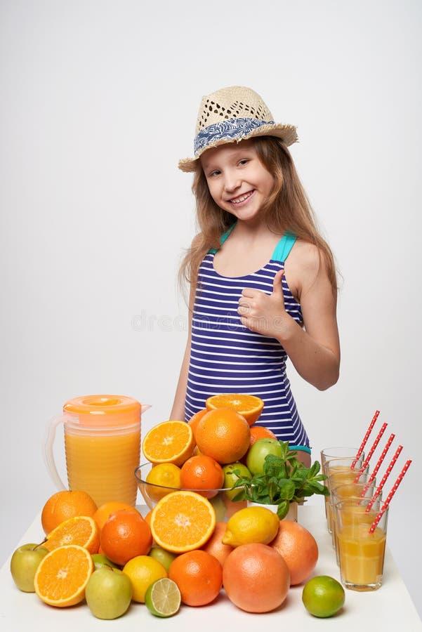 泳装和夏天帽子的女孩用很多柑橘水果和橙汁 库存照片