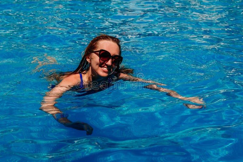 泳装和太阳镜的一微笑的年轻女人在与大海的一个室外水池游泳 免版税图库摄影
