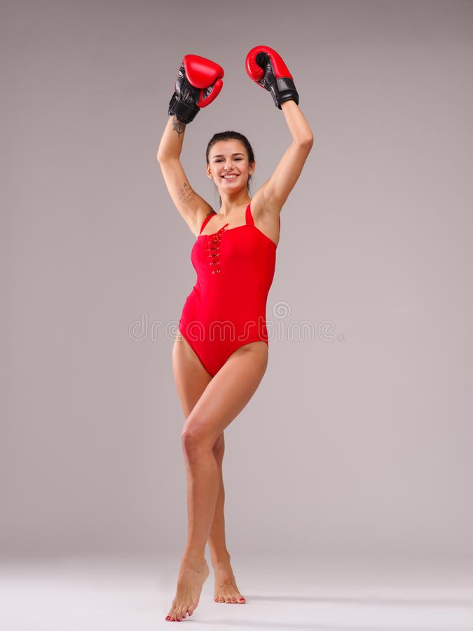 泳装的一个女孩有微笑的举了她的手反对灰色背景 免版税图库摄影