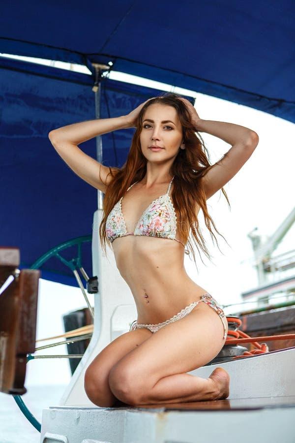 泳装的一名美丽的妇女坐游艇 免版税库存图片