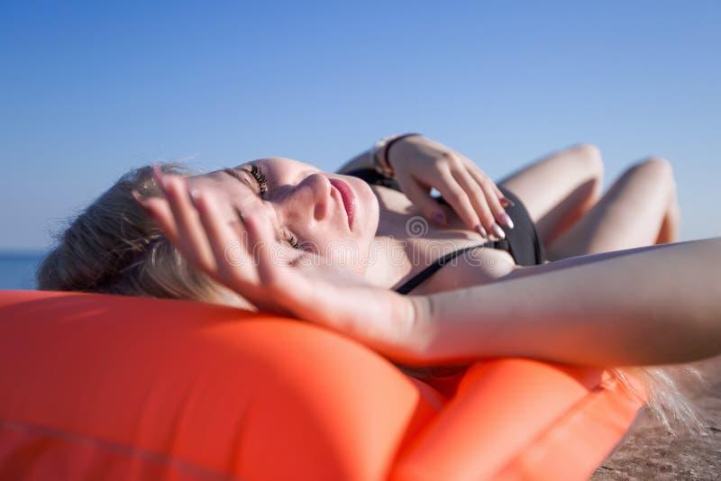 泳装的亭亭玉立的少妇在桃红色水池木筏晒日光浴 图库摄影