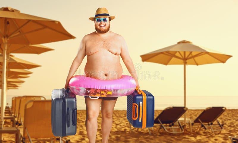 泳装的厚实的人有一个手提箱和橡胶环的以夏天海滩为背景 免版税库存图片