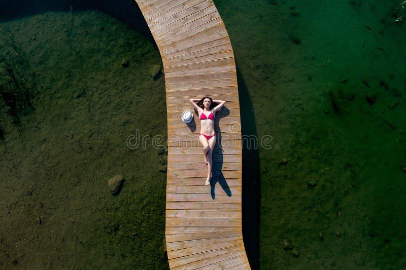 泳装的妇女晒日光浴在码头的 免版税库存图片