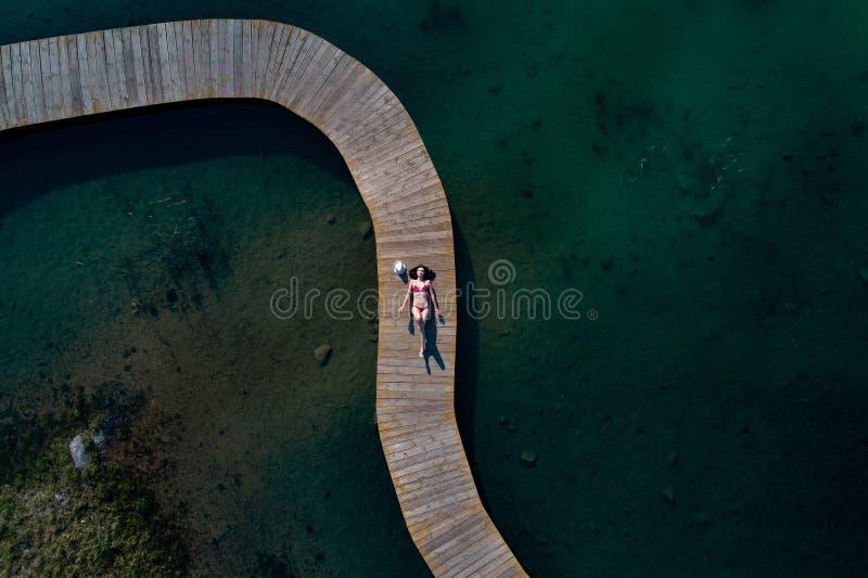 泳装的妇女晒日光浴在码头的 免版税图库摄影