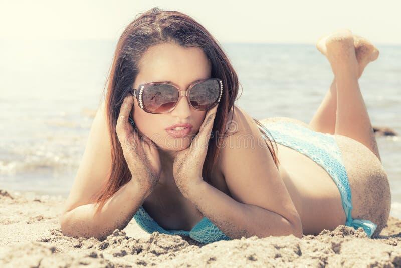泳装的少妇在与太阳镜的沙子 免版税库存照片
