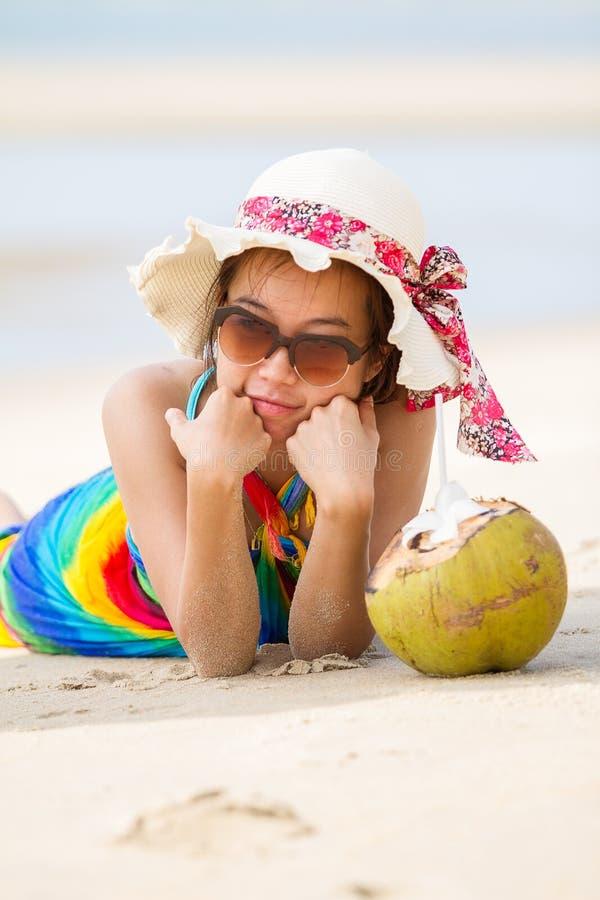 泳装的少妇有椰子鸡尾酒的 免版税库存图片