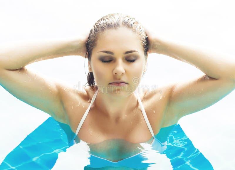 泳装的年轻和运动的妇女 放松在水池的女孩在夏天 免版税库存图片