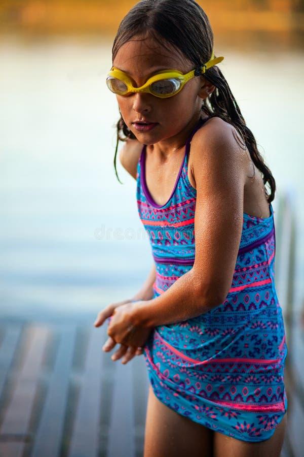 泳装的游泳者女孩和游泳的玻璃有锻炼在湖 图库摄影