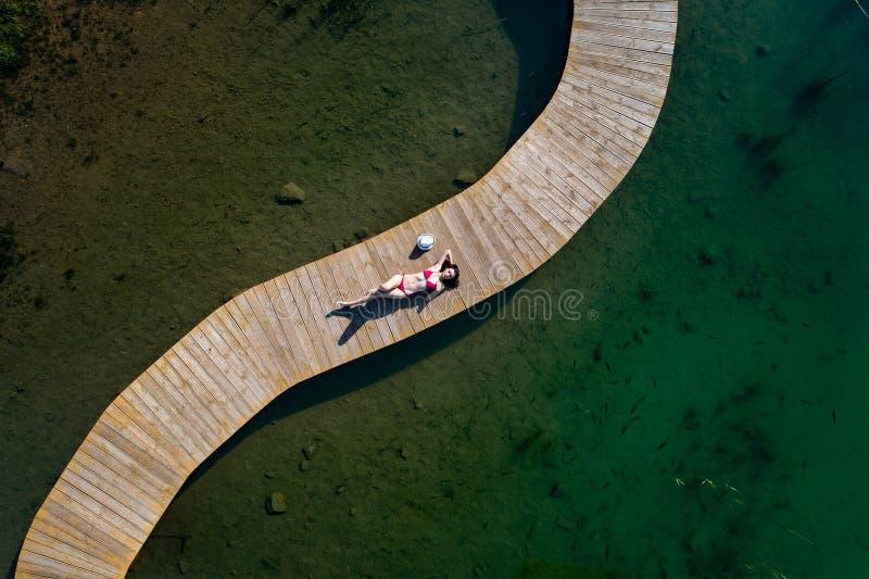 泳装的空中寄生虫视图妇女晒日光浴在码头的 免版税库存图片