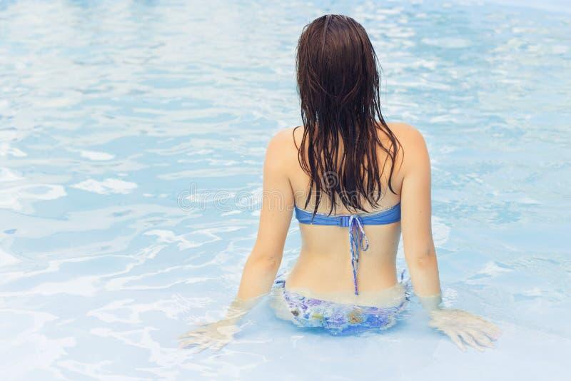 泳装的美丽的深色的妇女在放松单独的海滩 免版税图库摄影