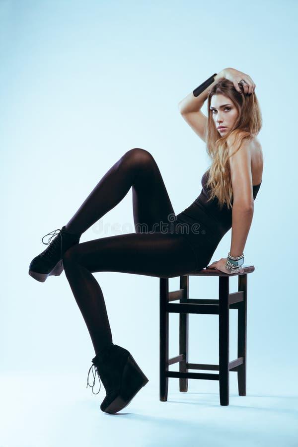 黑泳装的金发碧眼的女人坐摆在演播室的椅子 库存照片