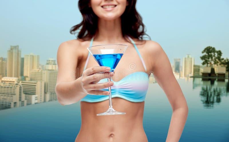 泳装饮用的鸡尾酒的愉快的少妇 免版税库存图片