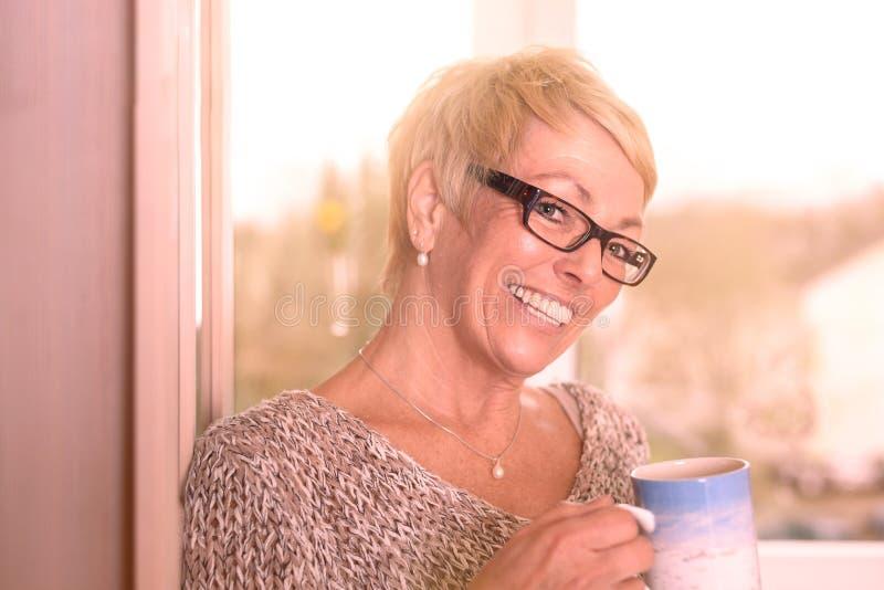 活泼的中年妇女饮用的咖啡 库存照片