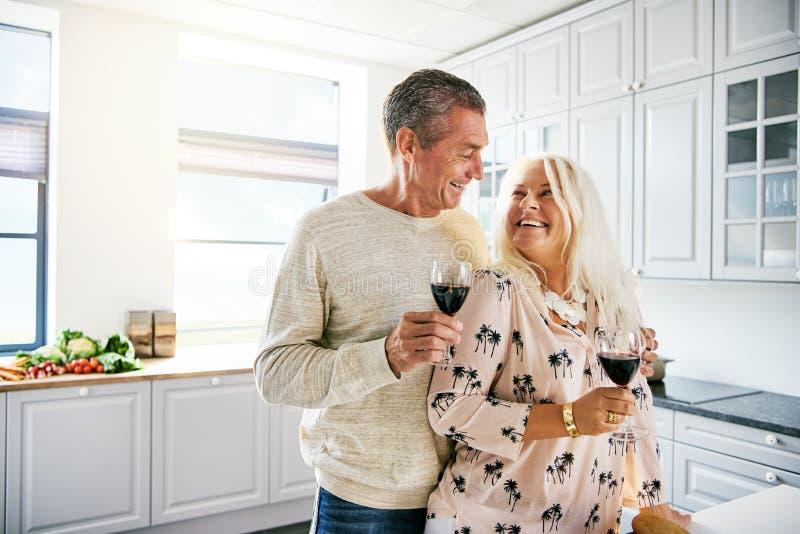 活泼的健康年长夫妇饮用的酒 免版税图库摄影