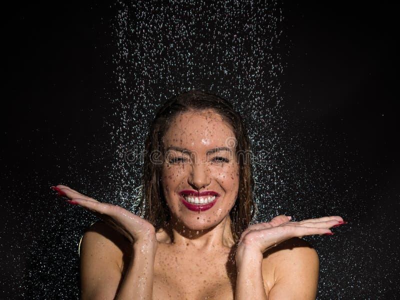 活泼的少妇获得乐趣在阵雨 免版税库存照片