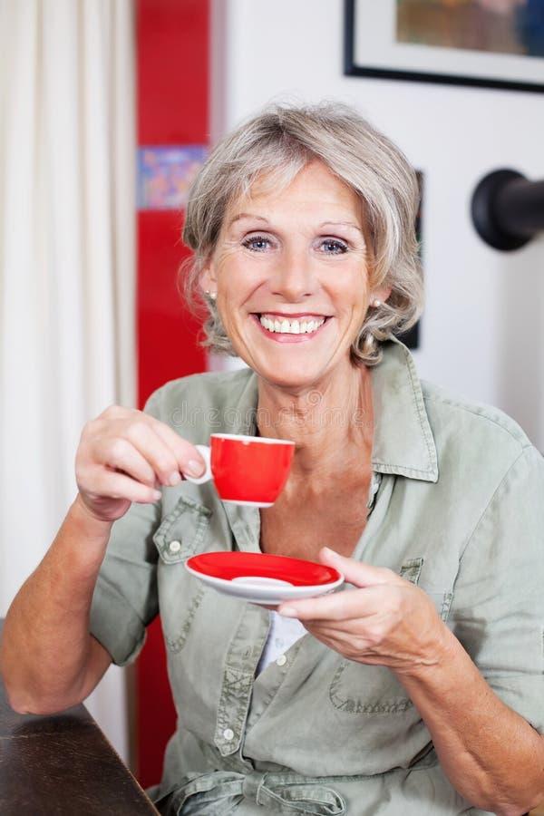 活泼的资深妇女饮用的浓咖啡 免版税库存照片