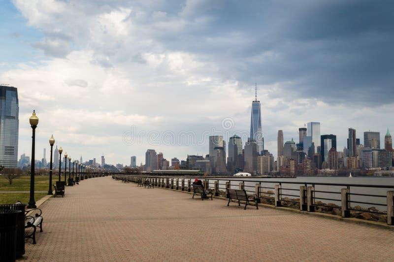 泽西市, NJ/美国- 2016年3月:自由国家公园春天多云天,与曼哈顿地平线的哈得逊河岸 免版税库存图片